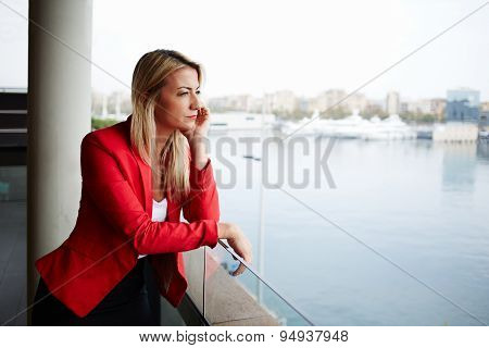 Businesswoman looking out of an office balcony with beautiful seaport view on background