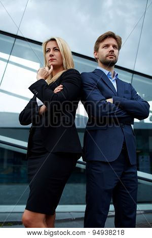 Two experienced and confident businesspeople crossing their arms while standing near office