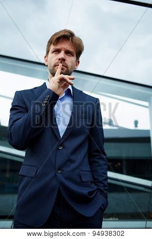 Portrait of young caucasian businessman gesturing silence with his finger on his lips