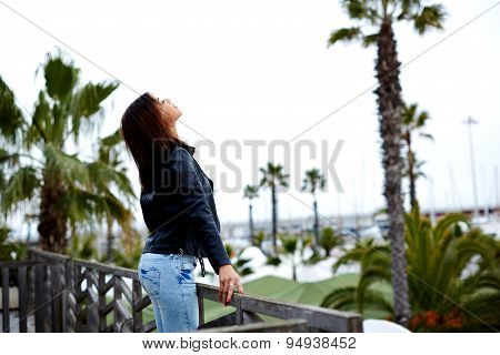 Attractive female enjoying the view while standing on the balcony during her vacation holidays