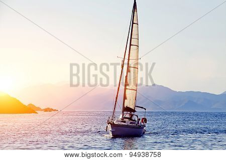 Beautiful racing yacht in the Mediterranean sea with blue sky and mountains on background