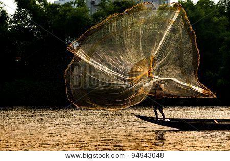Fishermen are throwing fishing net on river in Hue, Vietnam