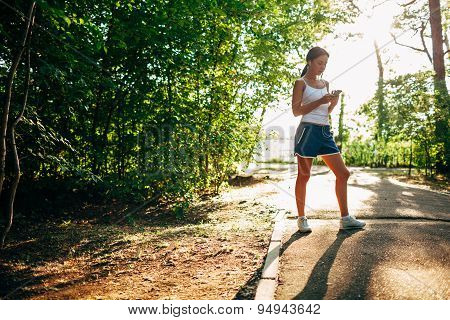 woman with audio player doing fitness in city park