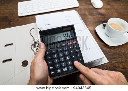 Person Hand Calculating Tax On Calculator