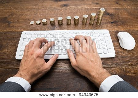 Businessman Using Keyboard In Front Of Stacked Coins