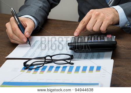 Businessperson Calculating Tax In Office