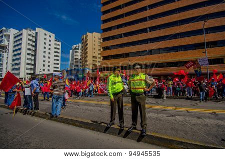 Two ecuadorian policemen wearing uniforms supervising protesters marching in the capital city Quito
