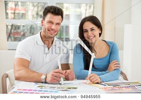 Young Couple With Model House Made Up Of Measurement Tape