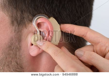 Hands Inserting A Hearing Aid Into A Man's Ear