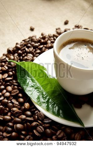 Macro Cropped Shot Of Frothy Coffee With Green Leaf On Linen Cloth