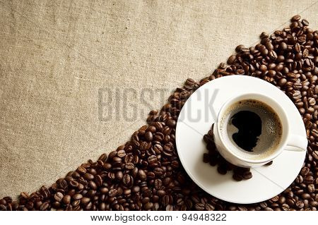 Frothy Coffee Cup With Beans In The Corner On Fabric Flax