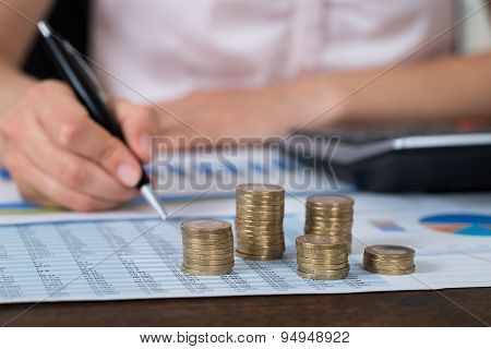 Businessperson With Coins Over Graph And Report