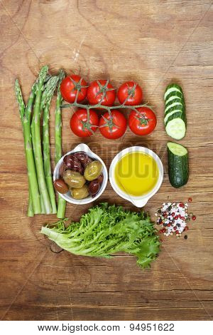 Healthy eating concept food set - asparagus, tomatoes, olives, oil, green salad, top view