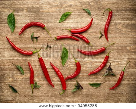 Red Hot Chili Peppers with herbs and spices over wooden background - cooking or spicy food concept