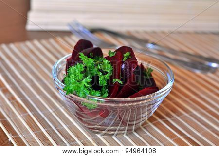 Sliced beetroot salad with parsley on a glass bowl on a wooden table