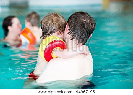 Young Dad Teaching His Little Son To Swim Indoors