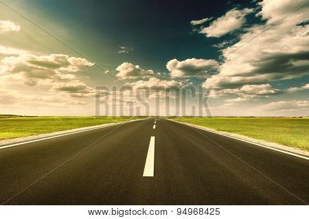 Driving Ahead On Straight Asphalt Road At Sunset