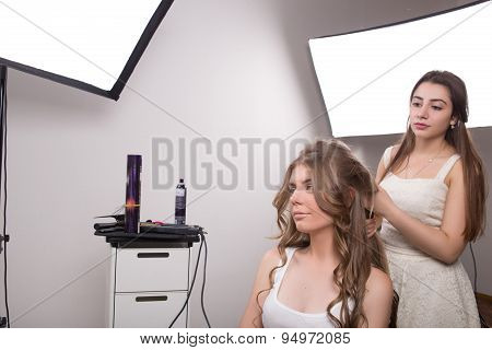 Hairdresser does hair style of woman in hairdressing salon.