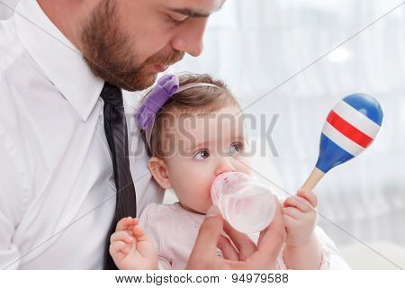 Pleasant father feeding baby