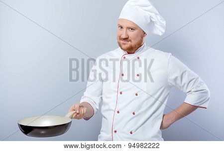 Head-cook holding pan and looking at camera