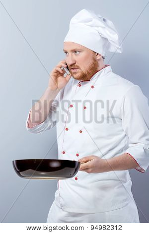 Head-cook holding pan and using phone