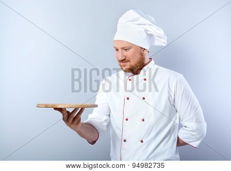 Head-cook holding wooden board for cutting