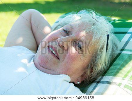 Female Senior Is Relaxing In The Garden