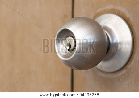 Old And Dirty Doorknob On Brown Wooden Door