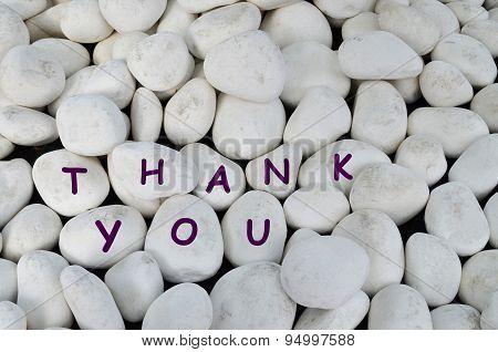 Thank you message written on white stones