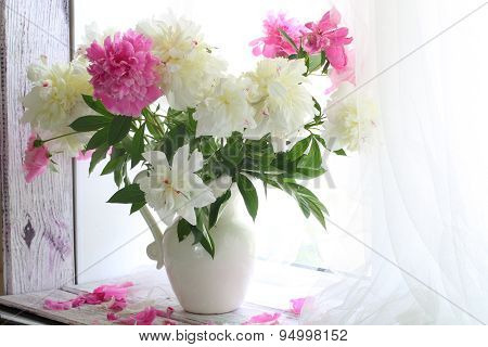 Bouquet Of White And Pink Peonies In A Jug On A White Window Sill