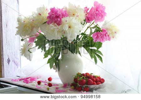 Strawberry In A Wattled Vase And A Bouquet Of Peonies On A White Window Sill