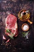 foto of ribeye steak  - Raw fresh meat Steak Ribeye and seasonings on dark metal background - JPG