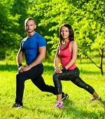 pic of stretch  - Man and woman doing stretching exercises at summer park - JPG