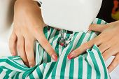 picture of sewing  - Seamstress sew fabric on the sewing machine - JPG