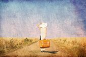 stock photo of old suitcase  - Redhead girl with suitcase at countryside road near wheat field - JPG