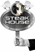 image of cow head  - Hand of chef holding a metal sign with text Steak house head of cow forks and spatulas - JPG