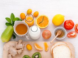 stock photo of orange  - Breakfast with orange juice oranges oranges slice passion fruit ginger tomato and Kiwi set up on wooden table  - JPG