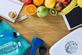foto of measurement  - Fitness and weight loss concept dumbbells white scale towels fruit tape measure and digital tablet on a wooden table top view - JPG