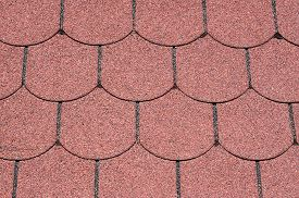 pic of shingles  - Roof with red bitumen shingles closeup in sunny day - JPG
