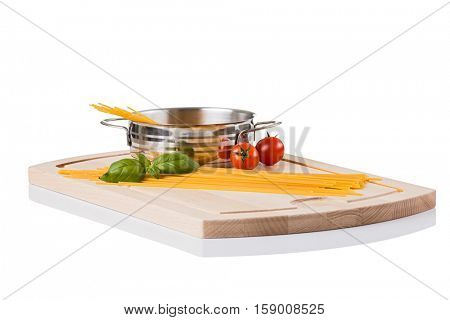 Raw pasta in metallic pot isolated on wooden board