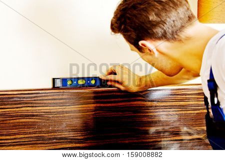 Young handyman with spirit level