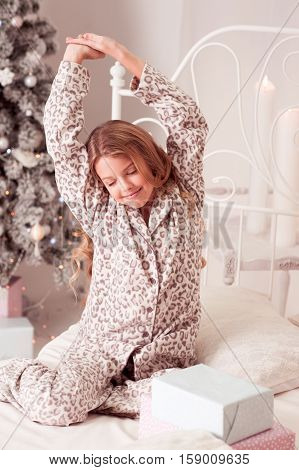 Kid girl 10-12 year old waking up in Christmas morning in bed. Stretching. Open Christmas presents. Eyes closed. Wearing pajamas.