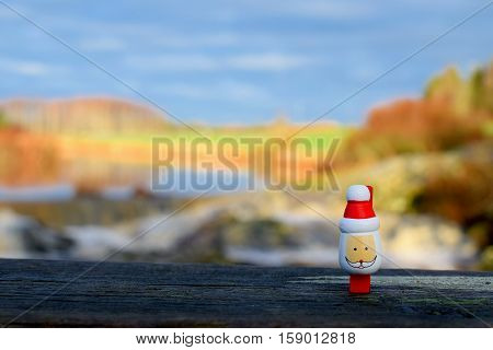 Small wooden Santa Claus with nature on background.