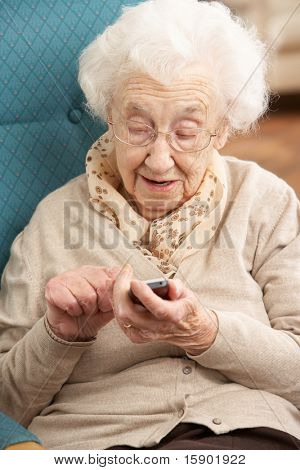 Senior Woman Dialling Number On Mobile Phone Sitting In Chair At Home