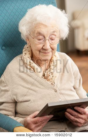 Sad Senior Woman Looking At Photograph In Frame