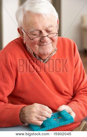 Senior Man Sorting Medication Using Organiser At Home
