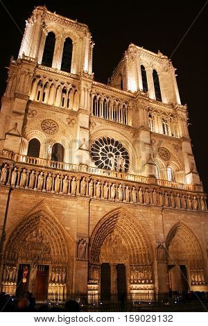 Evening in Paris and the lights on Paris's iconic Cathederale de Notre Dame come on illuminating the grand structure's gothic features. Numerous tourists are blurred by the long exposure.