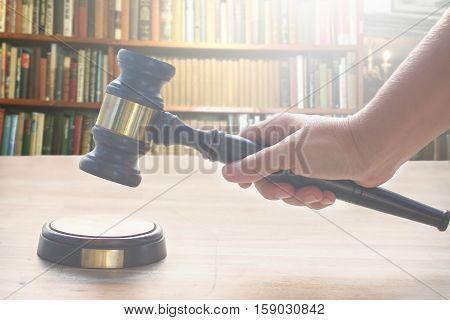 someones hand holding Wooden Law Gavel over wooden table