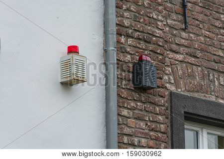 Two alarm systems with warning lights on a house wall