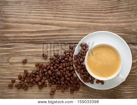 Coffee cup and coffee beans on old wooden background.